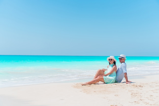 夏休み中に白いビーチで若いカップル。幸せな恋人たちは彼らの新婚旅行を楽しむ
