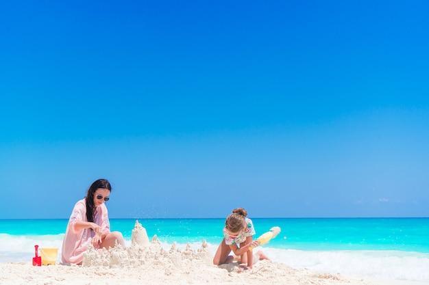 母と小さな子供が熱帯のビーチで砂の城を作る