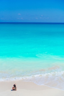 Молодая красивая девушка на пляже в неглубокой тропической воде вид сверху фон