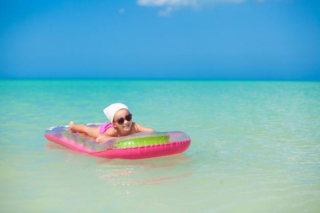 暖かい海でピンクのエアベッドで日光浴かわいい女の子