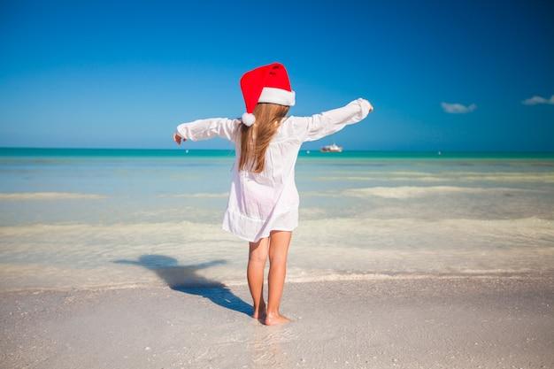 ビーチで赤い帽子サンタクロースでかわいい女の子の背面図