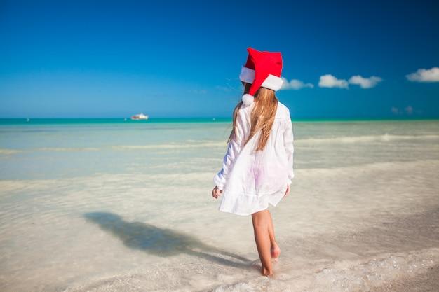 ビーチで赤い帽子サンタクロースでかわいい女の子
