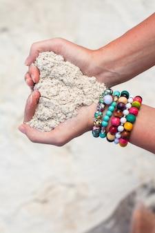 女性の手の中に砂の心のクローズアップ
