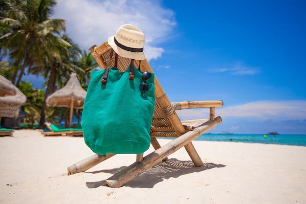 帽子と白い砂のビーチでバッグ木製ビーチチェア