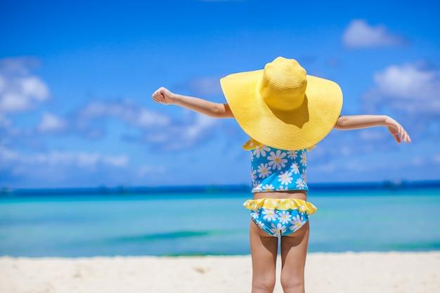 白い砂のビーチで海を見て大きな帽子の女の赤ちゃんの背面図