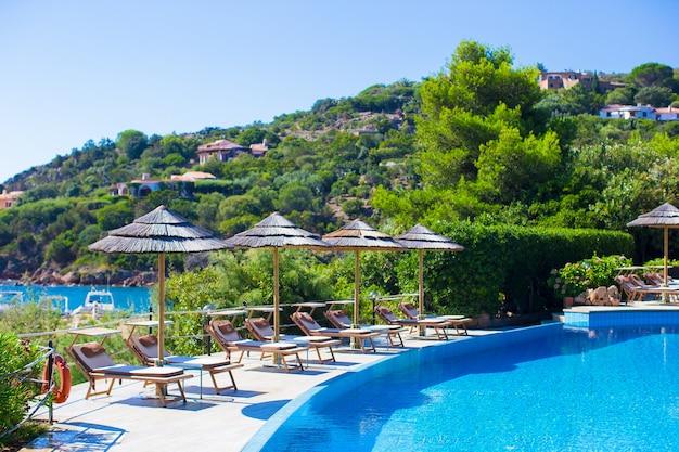 Деревянные шезлонги и зонтики возле бассейна бесконечности в роскошном курорте