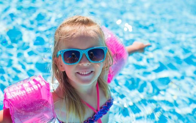 愛らしい幸せな女の子は、スイミングプールで楽しんでいます