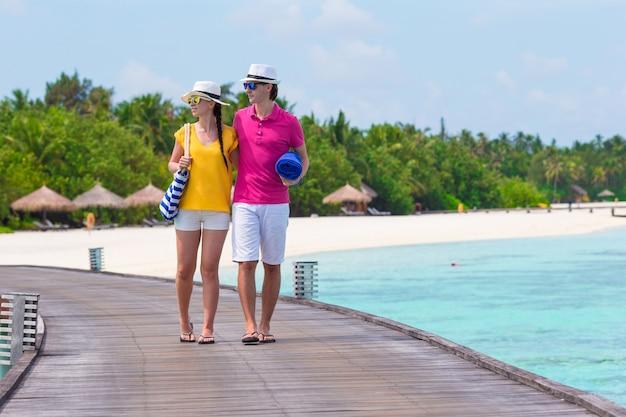 Пара на пристани тропический пляж собирается на пляж на мальдивах