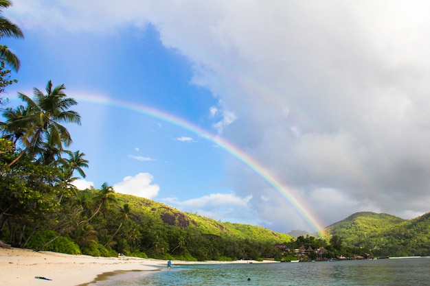 Радуга над тропическим островом и белым пляжем на сейшельских островах