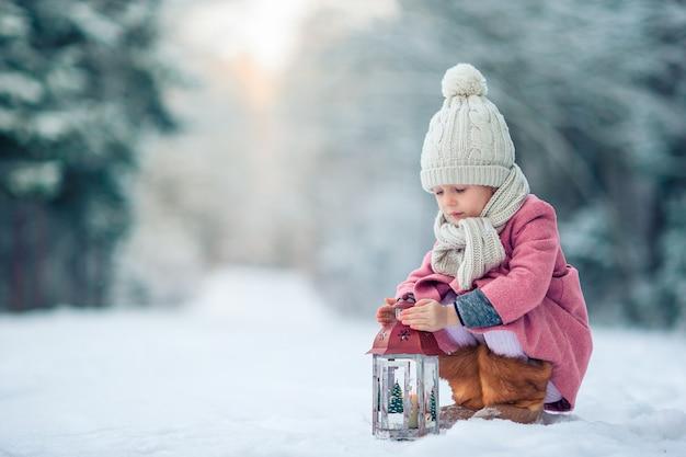 屋外のクリスマスに懐中電灯で愛らしい少女の背面図