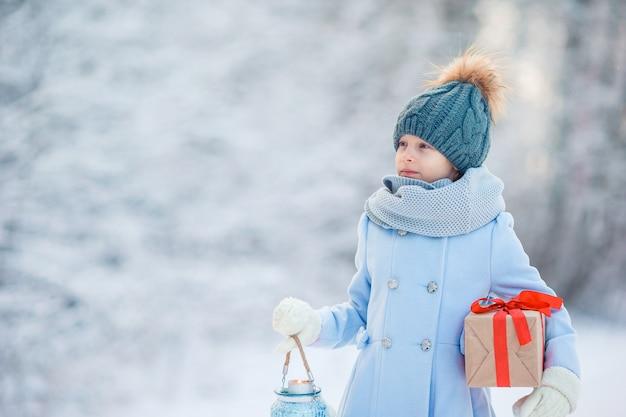 冬の屋外でクリスマスボックスギフトと愛らしい少女