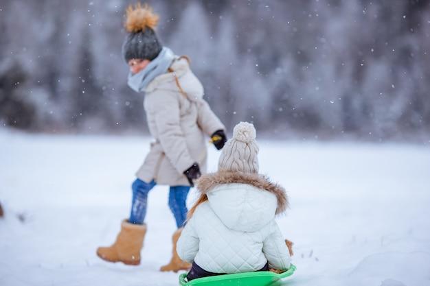 Очаровательные маленькие счастливые девочки, катание на санях в зимний снежный день.