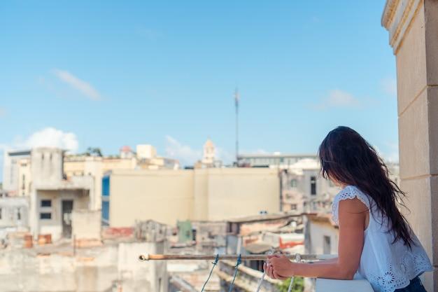 ハバナのアパートの古いバルコニーに若い魅力的な女性