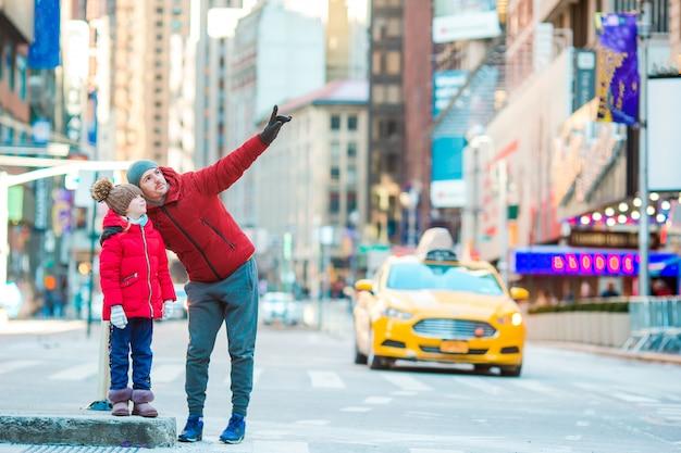 Семья отца и маленького ребенка на таймс-сквер во время их отпуска в нью-йорке