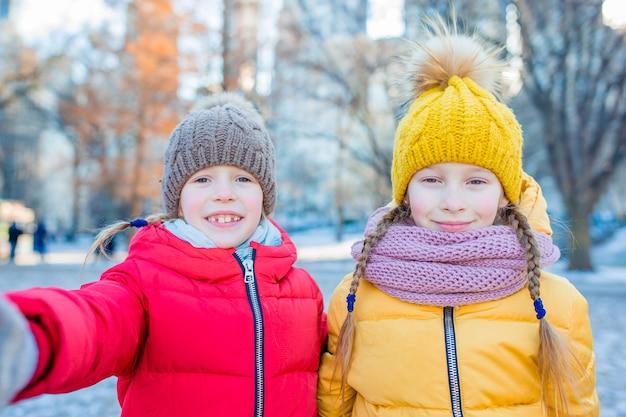 Восхитительные маленькие девочки, делающие фотографию селфи в центральном парке в нью-йорке