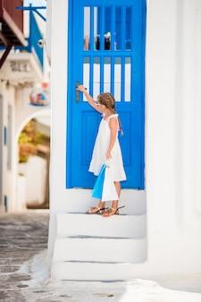 Красивая девушка на улице типичной греческой традиционной деревни на миконосе