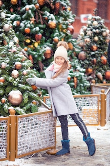 新年の雪の中でモミの木の枝の近くの小さな幸せな女の子。