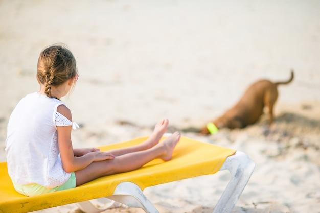 Счастливая маленькая девочка на пляже, играя с собакой