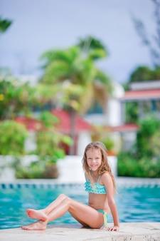 愛らしい少女は屋外スイミングプールの近くで楽しい時を過す