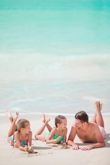 父とビーチ夏の熱帯の休暇を楽しんでいる小さな子供たち