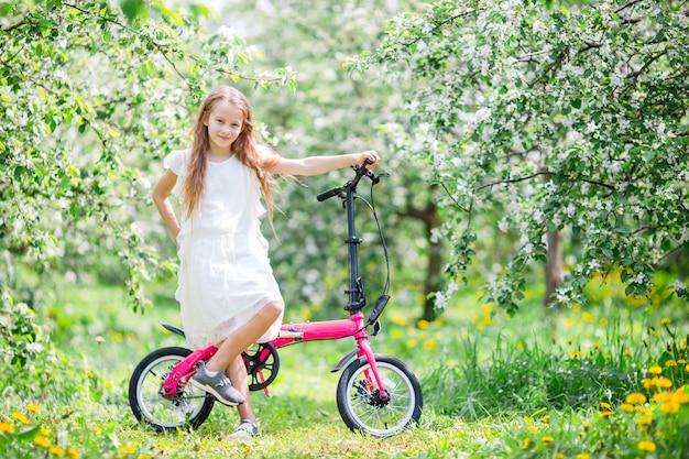 美しい夏の日の屋外で自転車に乗って愛らしい少女