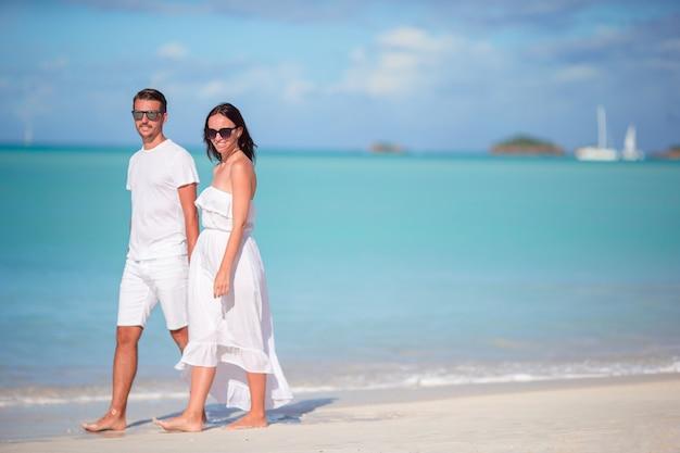 アンティグア島で白い砂浜とターコイズブルーの海の水と熱帯のカーライル湾ビーチを歩く若いカップル