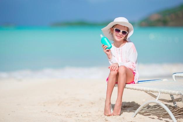 熱帯のビーチで日焼け止めクリームのボトルと美しい子供
