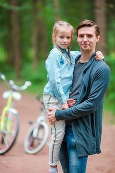 Счастливая семья на велосипеде на открытом воздухе в парке