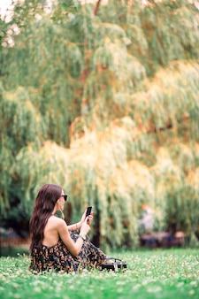 かわいい女性は、公園に座って携帯電話でテキストメッセージを読んでいます。