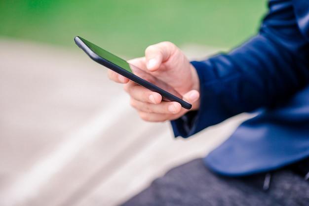 男性の手のクローズアップは、路上で屋外で携帯電話を保持しています。モバイルスマートフォンを使用している人。