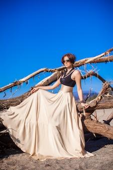 ビーチで美しいドレスの愛らしい若い女性