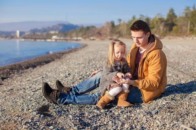 若い父親と晴れた冬の日にビーチで彼の小さな娘