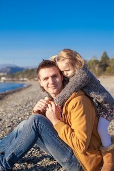ビーチで小さな女の子と若い父親は晴れた冬の日に楽しい時を過す