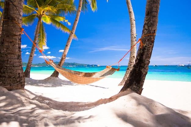 熱帯の白いビーチで居心地の良いわらハンモックのビュー