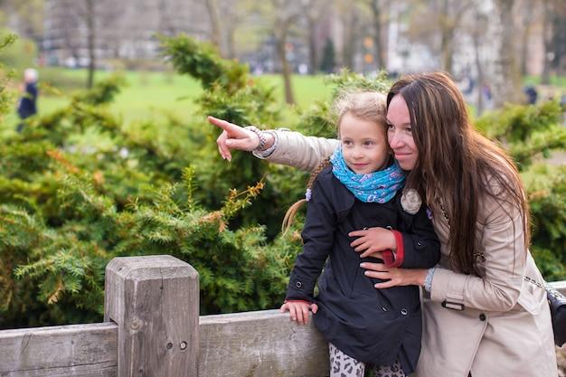 Молодая мать и ее дочь на прогулке в центральном парке