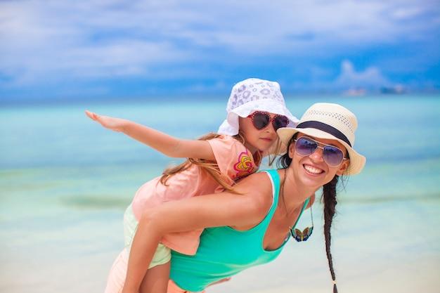 若い母親と彼女の愛らしい小さな娘は、熱帯のビーチで楽しい時を過す