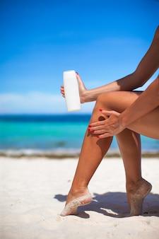 女性は滑らかな日焼けした足にクリームを塗る