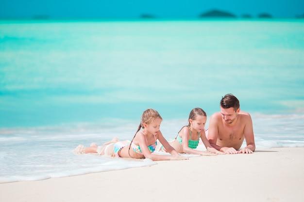 Отец и маленькие дети наслаждаясь каникулами лета пляжа тропическими. семья играет на пляже
