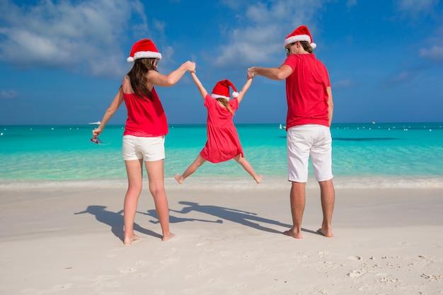 白いビーチで楽しんでクリスマス帽子で幸せな家族