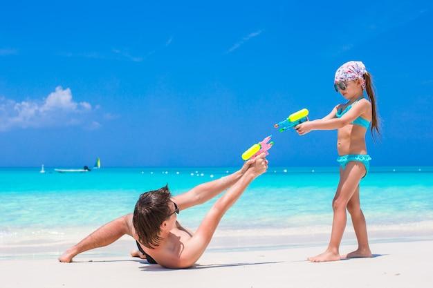 ビーチでの休暇を楽しんでいる彼の小さな子供と幸せな父