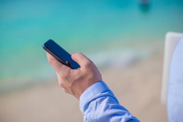 熱帯のビーチに手で電話を持ったビジネスマン