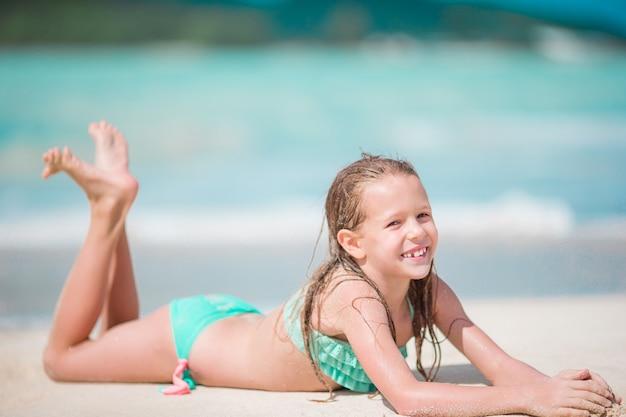 Прелестная маленькая девочка лежа в мелководье на белом пляже