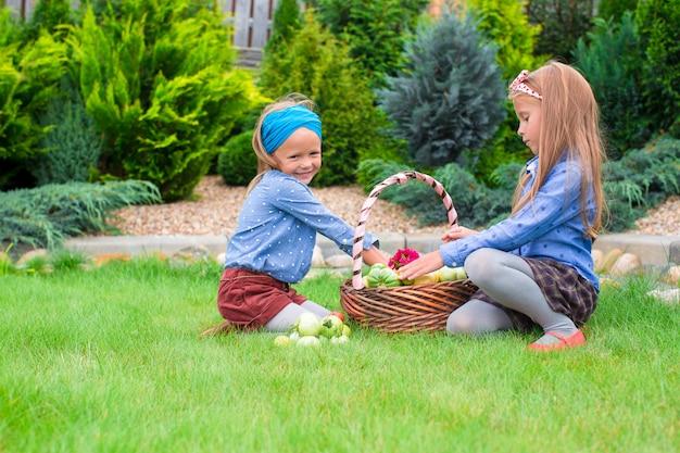 Две маленькие счастливые девочки с большим осенним урожаем помидоров в корзинах