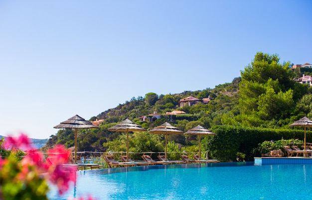 Деревянные шезлонги возле бассейна бесконечности в роскошном курорте