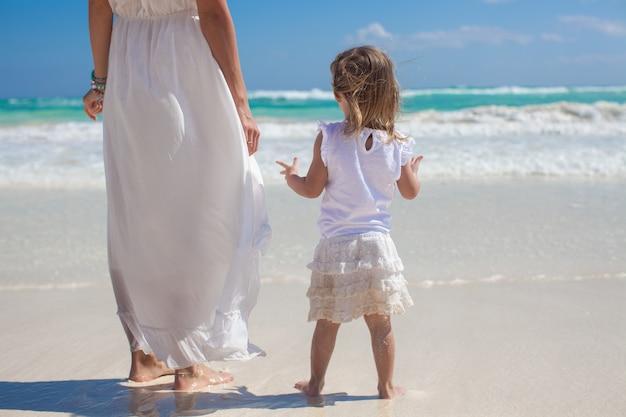 Вид сзади матери и его маленькой дочери, глядя на море на тропическом пляже