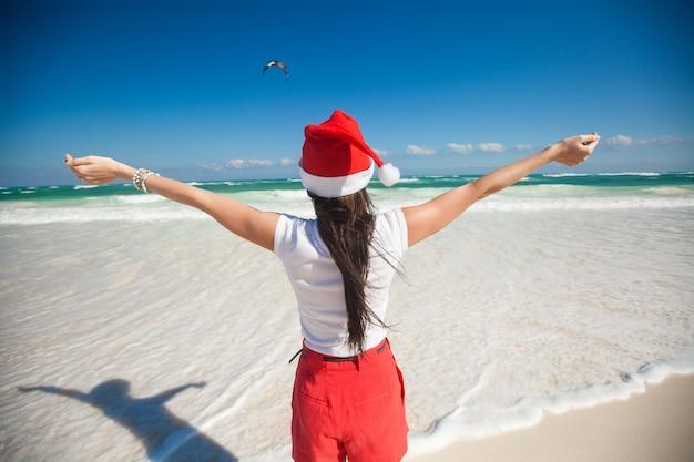 白いビーチで鳥のように歩くサンタ帽子で美しい少女の背面図