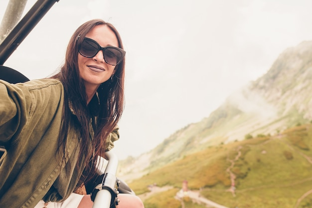 霧の背景の山の美しい幸せな若い女性