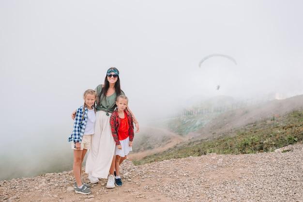 霧の背景の山の美しい幸せな家族。美しい風景