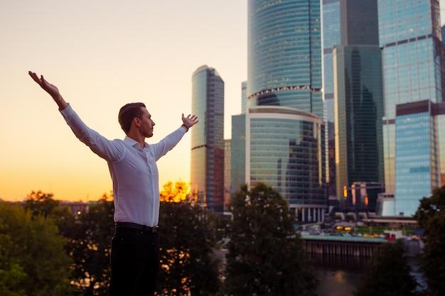 ガラスの超高層ビルに対して立ちながらコピースペースを探しているビジネスマンの背面図