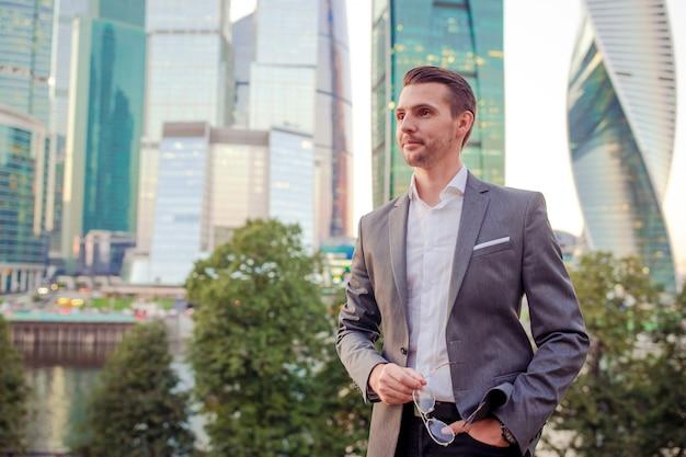 ガラスの超高層ビルに対して立っている間コピースペースを探しているビジネスマン